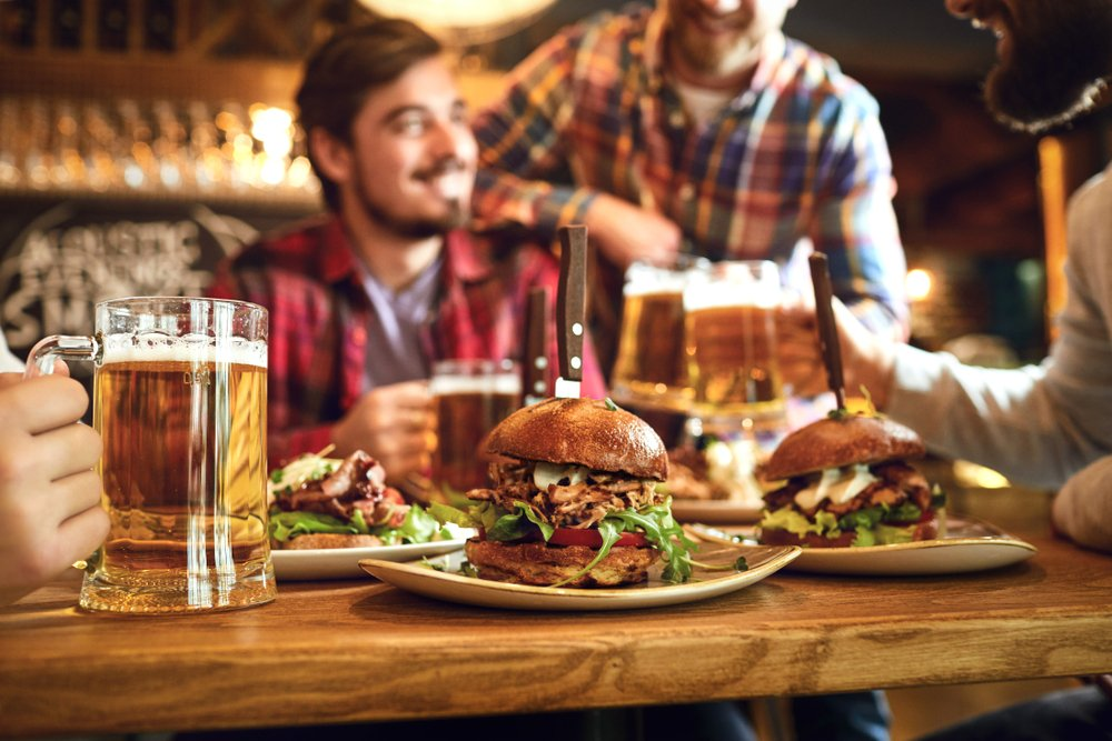 friends eating burger and drinking beer at a restaurant in Asbury Park